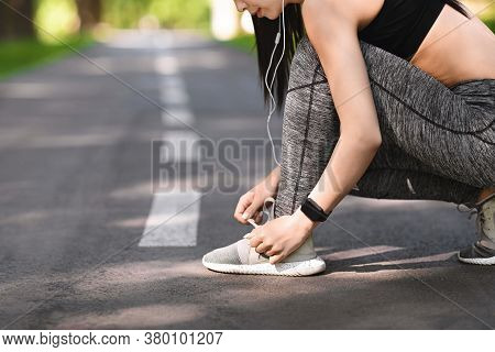 Sporty Girl Tying Shoes Laces Before Running, Getting Ready For Jogging Outdoors In Park, Cropped Im