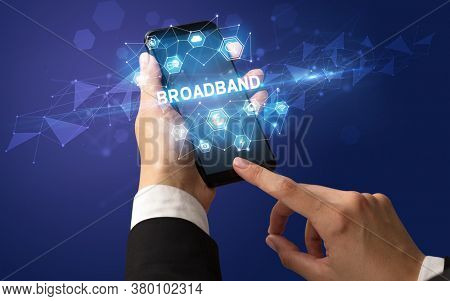 Female hand holding smartphone with BROADBAND inscription, modern technology concept