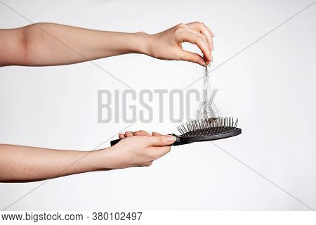 Females Hands Clean The Comb From Fallen Hair. Close Up. White Background. Concept Of Hair Loss, Bal