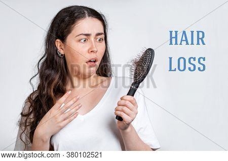 Hair Loss. A Terrified Brunette Woman Holds A Comb In Her Hands, With A Bunch Of Hair That Has Falle