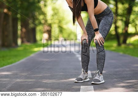 Cropped Image Of Female Jogger Taking Breath After Running In Park, Putting Hands On Knees, Resting