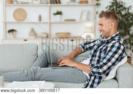 Side View Of Young Happy Man Chatting Online On Laptop With Friend At Home, Lying On Couch In Light