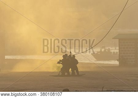 Military Combat Helicopter Rescue Team On The Ground With A Rope In The Smoke And Haze.