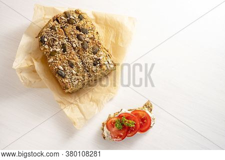 Low Carb Protein Bread With Seeds On Baking Paper And A Tomato Sandwich With Parsley Garnish On A Wh