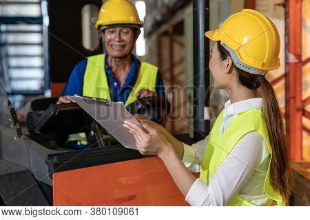 Female young asian warehouse workers discuss about inventory to male worker who operate forklift in large distrubution warehouse background. Reopening business warehouse inventory and logistic concept
