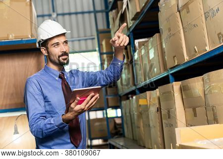 White caucasian middle east warehouse manager hold digital tablet to do inventory in warehouse distribution center environment.  For business warehouse inventory and logistic concept.