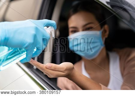 Medical staff give alcohol gel hand sanitiser to asian woman before coronavirus covid-19 test at drive thru station in hospital. New normal healthcare drive thru service and medical concept.