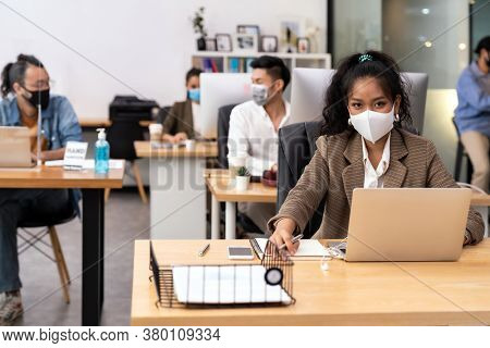 Portrait mixed race of African black and asian office worker wear face mask working in new normal office with social distance to Group of business team people to prevent coronavirus COVID-19 spreading