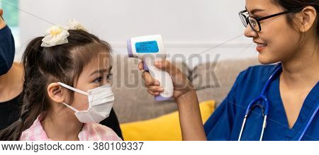 Panoramic Asian female doctor use infrared thermometer to take temperature to little girl child in living room while doctor visit at home. Home health care delivery and doctor visiting concept.