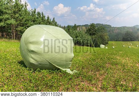 Agricultural Landscape In Czech Republic With Straw Packages On Field. Cereal Bale Of Hay Wrapped In