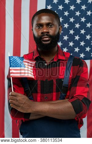 Young bearded African-american worker in flannel and overalls holding flag while standing against stars-and-stripes background