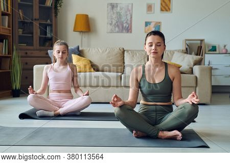 Relaxed brunette female and her teenage daughter in tracksuits sitting on mats in pose of lotus while taking yoga course for beginners at home