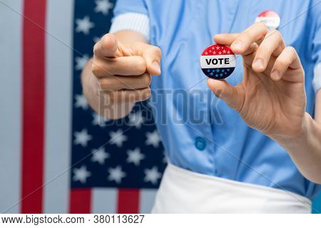 Hands of young contemporary chambermaid or housewife showing vote insignia and pointing at you against stars-and-stripes flag