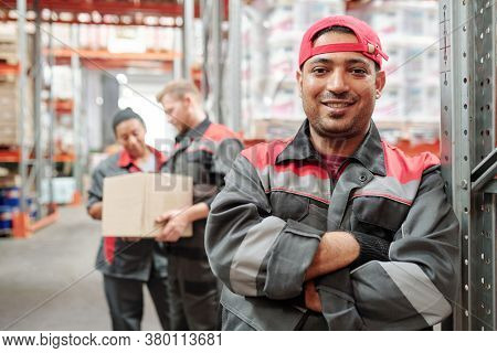Happy young Latino man in workwear and gloves crossing arms by chest while standing against his colleagues working in warehouse