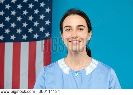 Young confident chambermaid in blue uniform looking at you with smile while standing in front of camera against stars-and-stripes flag