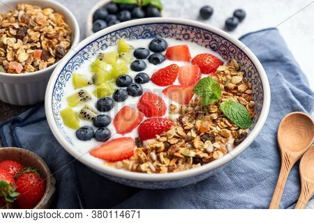 Yogurt With Granola, Blueberries, Strawberries And Slices Of Kiwi In A Bowl. Closeup View. Healthy B