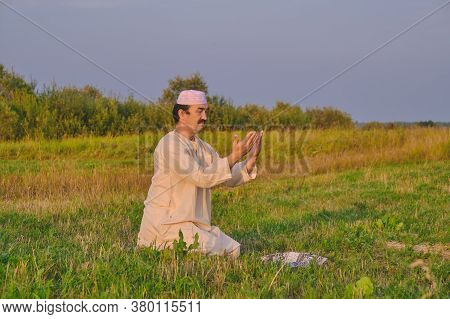 A Muslim Senior Man Wearing An Embroidered Skullcap And White Traditional Clothes Prays In An Hayfie
