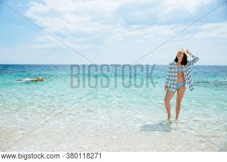 Woman In Blue Checked Shirt Walking By Sea Beach