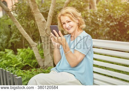 Aged Pretty White Woman About 60 Years Old Is Using Her Smartphone While Sitting On The Bench In Pub