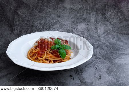 White Plate With A Portion Of Delicious Italian Spaghetti With Fresh Basil Leaves And Grated Parmesa
