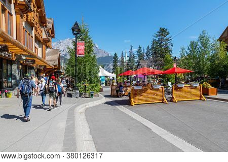 Banff, Canada - July 29, 2020: Tourists Walk And Dine Along Banff Avenue In Banff National Park. The