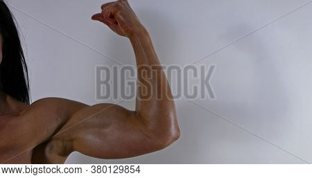 Strong muscular woman showing her biceps