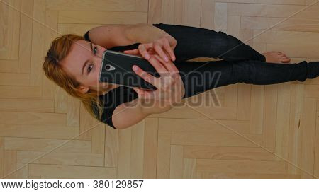 Young woman making selfie, she taking photo herself while sitting home.