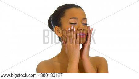 Young beautiful woman massaging or applying cream on her face, isolated on white.