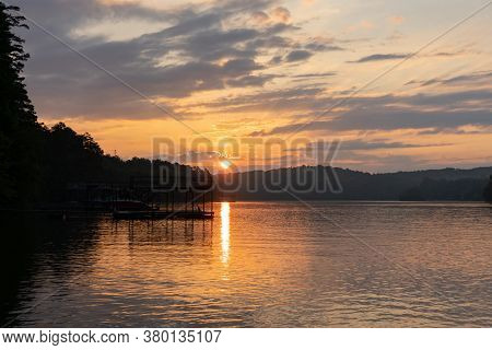 The Sun Rises Over Lake Lanier In Georgia, Showing A Reflection On The Water Under An Orange Cloudy