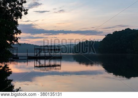 Silhouette Of A Dock On A Lake Before Dawn Under A Purple Sky In Summer; Landscape