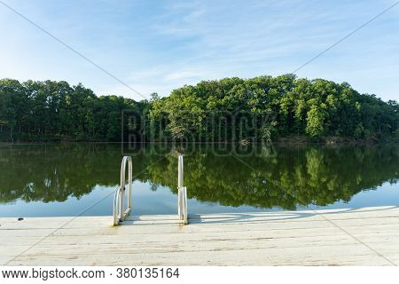 A Swim Ladder On A Dock On Lake Lanier In Georgia With A Reflection Of Green Trees In The Water; Sum