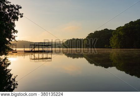 Fog On Lake Lanier In Georgia At Sunrise With The Silhouette Of A Dock; Landscape