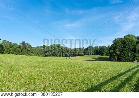 Rolling Green Hills Underneath A Bright Blue Sky In A Field In Georgia; Landscape