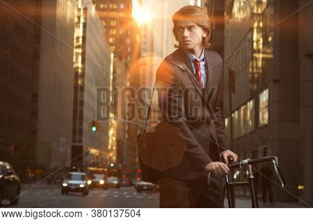 Handsome brunette business man commuting to work by bicycle wearing suit and tie