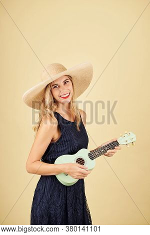 Portrait Of Smiling Pretty Blond Young Woman In Straw Hat Playing Ukulele, Isolated On Yellow