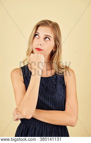 Studio Portrait Of Pensive Blond Young Woman Looking Up