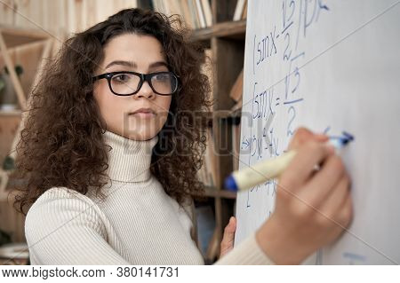 Young Serious Female Latin Math School Teacher Wearing Glasses Holding Writing Equation On Whiteboar