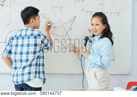 Vietnamese Math Teacher Speaking In Microphone And Explaining New Topic When Student Writing Equatio