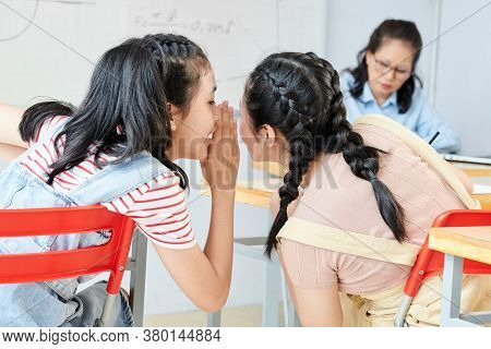 Teenage Vietnamese Schoolgirl Whispering Right Answer In Ear Of Her Classmate