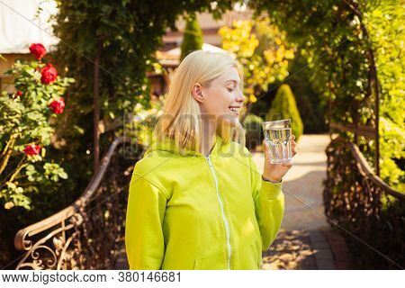 Stay Hydrated. Enjoy Every Sip Of Crystal Clear Water In Blooming Garden. Girl Drink Water. Woman En