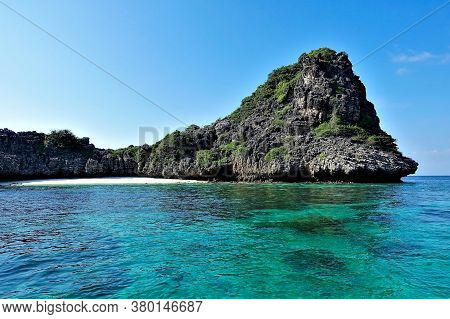 Secluded Beach On The Island. A Semicircular Strip Of Sand Is Surrounded By A Rock. The Clear Aquama