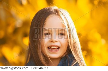Close Up Portrait Of Adorable Happy Baby Girl On Fallen Leaves Up, Playing In The Autumn Park Outdoo