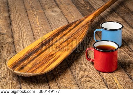 vintage wooden canoe paddle  on weathered wood picnic table with metal cups of tea