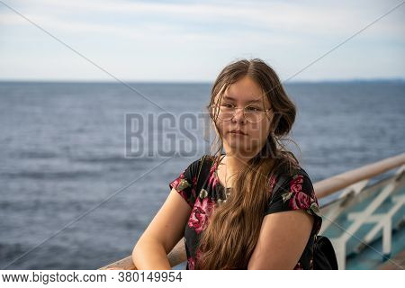 Photo Of A Young Preteen Girl With Long Brown Hair. Blue Ocean And Sky Background