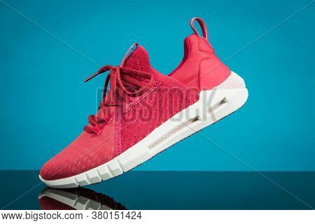 Running Sports Shoe On Blue Background. Running Shoe, Sneaker Or Trainer. Women's Athletic Shoe. Fit