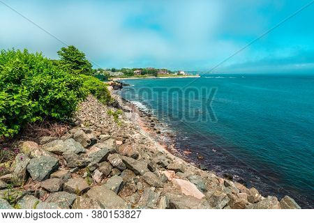 Blue Beach With Rocks And Houses On The Shore With Copy Space Fo