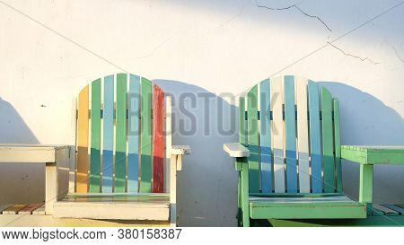 An Empty  Colorful Beach Chairs With Warm Light And White Wall Background In Outdoor Space
