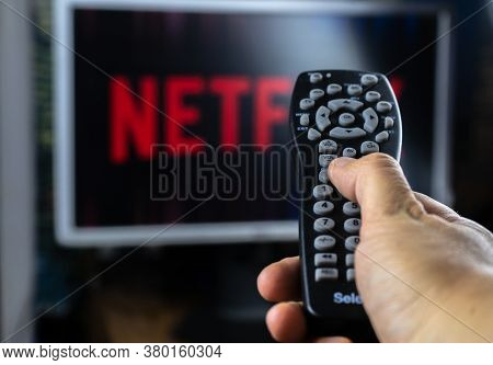Tv Remote Control In Front Of Tv Screen With Netflix Logo