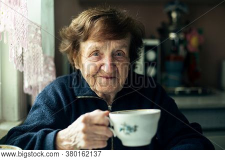 Close-up portrait of an elderly woman drink tea in her home.