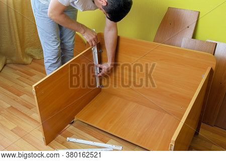 Man Collecting Computer Table Joining Parts Screwing Them Together With Bolts, Hands Closeup. Man Is